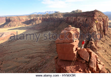 A man belays his climbing partner on Fisher Towers in Utah. - Stock Photo