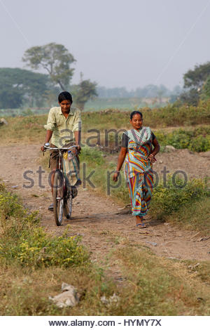 A man cycles past a women on a small dirt track on the outskirts of Kolkata. - Stock Photo