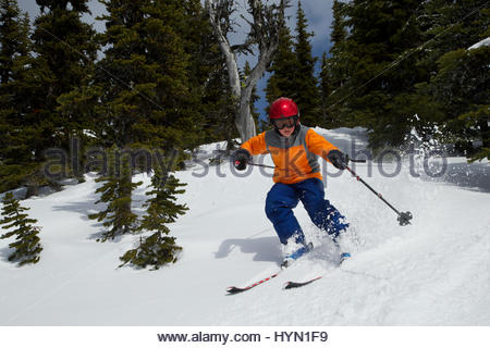 A young boy skiing down Whistler Mountain. - Stock Photo