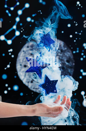 Reaching for stars: a hand with falling stars and smoke - Stock Photo
