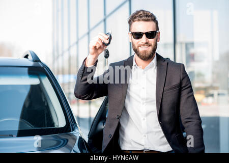 Man with keys near the car - Stock Photo