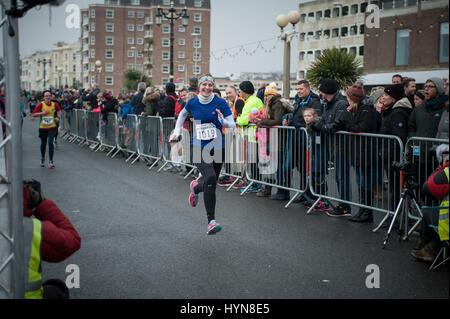 A women smiles and sprints for the finish line during the Worthing Half Marathon in Worthing, West Sussex, UK. - Stock Photo