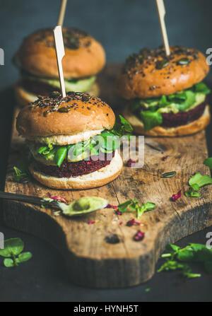 Healthy vegan burger with beetroot-quinoa patty, arugula on board - Stock Photo