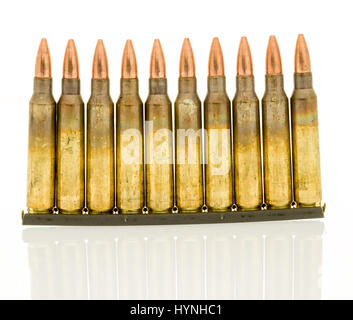 Ammunition of 5.56mm NATO round on a standard military clip for faster loads into a magazine - Stock Photo