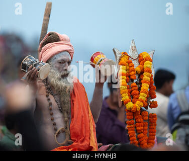 An old bearded man (Sadhu) wearing traditional outfit poses to a photo   in Varanasi, India. - Stock Photo