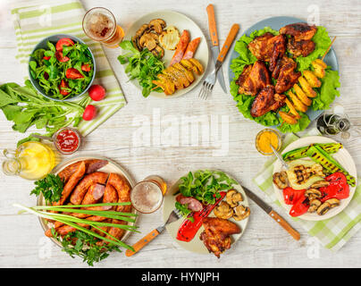 Dinner table with variety food, fried chicken wings, sausages, grilled vegetables in a pan, salad and  lager beer - Stock Photo