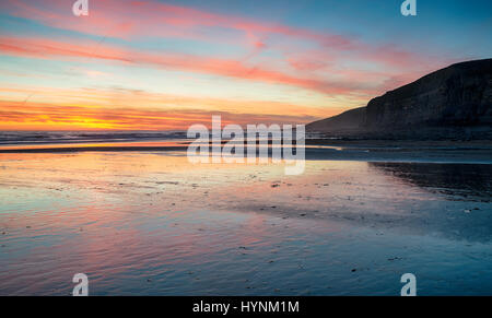 Sunset over the beach at Dunraven Bay near Bridgend in Wales - Stock Photo