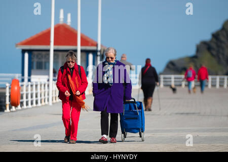 Aberystwyth Wales, UK. 6th Apr, 2017. UK Weather:  People walkingon the promenade in Aberystwyth on the shores of - Stock Photo