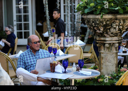 Florida, USA. 22nd Mar, 2017. A man reads menu at a restaurant in Worth Avenue on Palm Beach, Florida, the United - Stock Photo