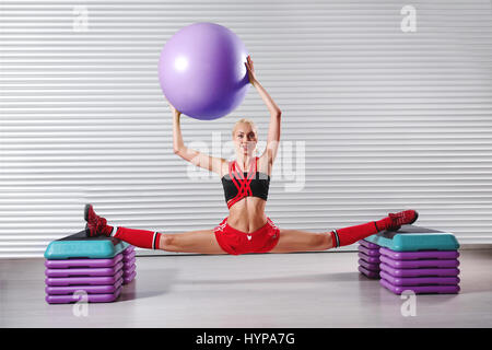 Beautiful young flexible fitness woman doing splits during her w - Stock Photo