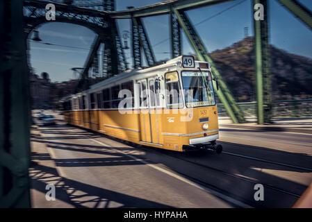 A tram crossing Liberty bridge in Budapest. - Stock Photo