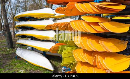 Rental kayaks and canoes on the riverbank at Welna River Wielkopolska - Stock Photo