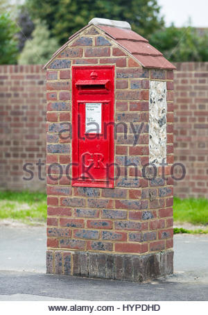 Red Royal Mail post box mounted in a brick construction in the UK. - Stock Photo