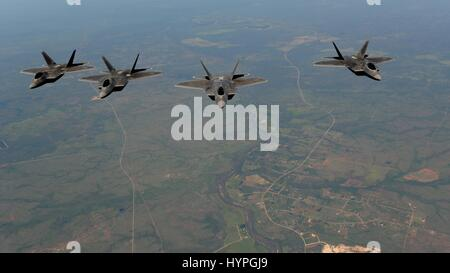 Four USAF F-22 stealth tactical fighter aircraft fly in formation over the Royal Australian Air Force Base Tindal - Stock Photo