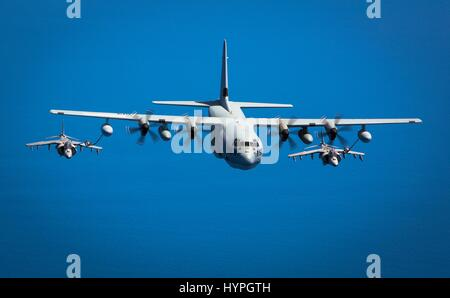 Two Spanish Navy AV-8B Harrier attack aircraft fly behind a USMC KC-130J tanker aircraft during an aerial refueling - Stock Photo