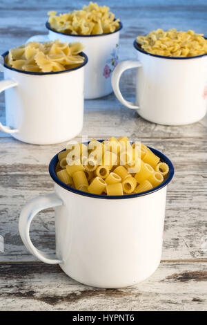 dried pasta in cup metallic fingering front - Stock Photo