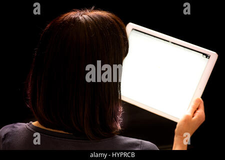 Woman looking at iPad Pro held in hand against black background - Stock Photo