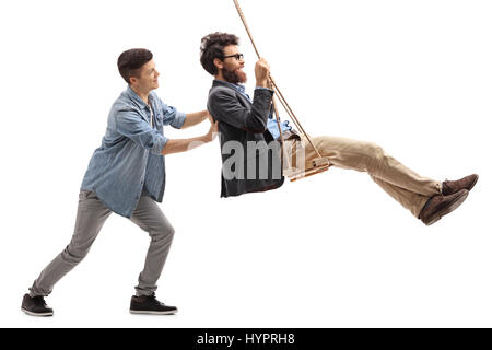 Full length profile shot of a son pushing his father on a swing isolated on white background - Stock Photo