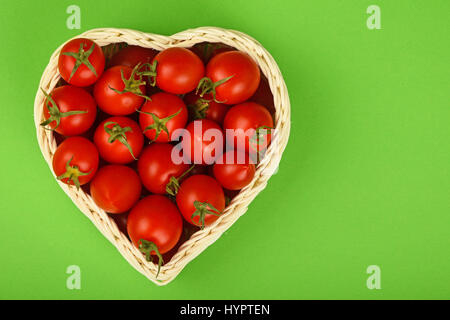 Red ripe fresh cherry tomatoes in small heart shaped wicker basket on green paper background - Stock Photo