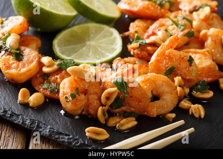 Fried prawns with peanuts, lime and greens macro on the table. horizontal - Stock Photo