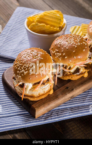 Homemade Mini Beef Burgers with Coleslaw Salad on Little Wooden Cutting Board. Barbecue Meat Sandwiches on Rustic - Stock Photo