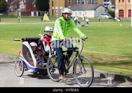 Woman cyclist on bike / bicycle with + 3 children; Co Pilot child seat with helmet & towing cycle Chariot trailer - Stock Photo