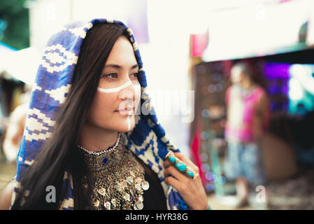 Female music festival attendee in costume and face paint. - Stock Photo