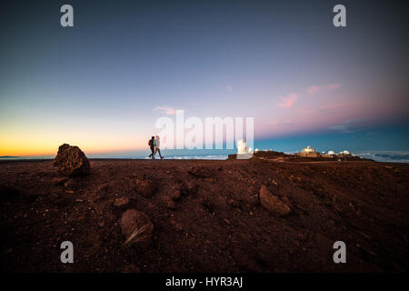 Hikers walking the trail atop the Haleakala crater in Maui with the High Altitude Observatory in the background, - Stock Photo