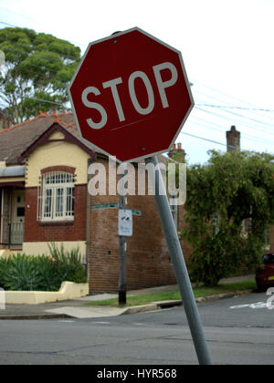 Red stop sign tilted to one side in Australia. Stop road sign to warn drivers. - Stock Photo