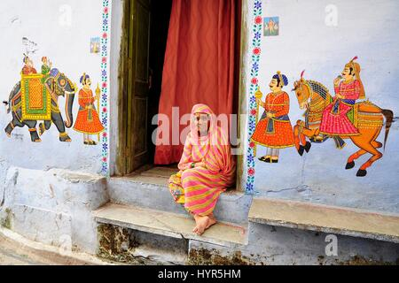 Udaipur, India, september 12, 2010: Old indian woman sitting in front of her huse on a ground with paintings on - Stock Photo