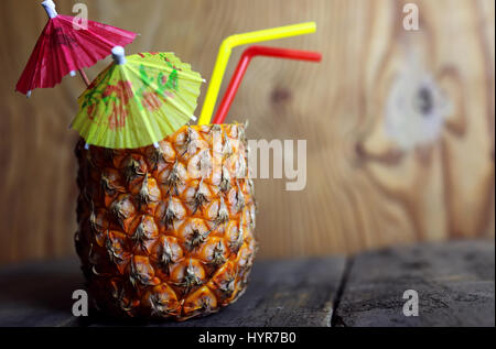pineapple with straw wooden background - Stock Photo