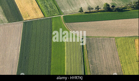 Freshly plowed and sowed farming land from above, neatly cultivated in non-urban agricultural area, textured effect - Stock Photo