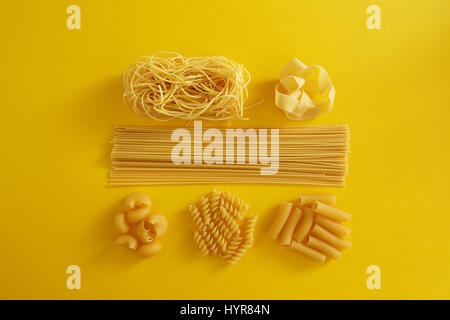 Assorted types of pasta on yellow background. Various forms of pasta. - Stock Photo