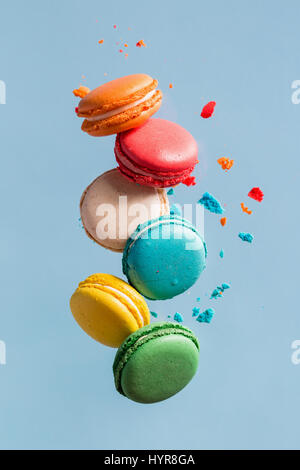 Different types of macaroons in motion falling on light  blue background. Sweet and colourful french macaroons falling - Stock Photo