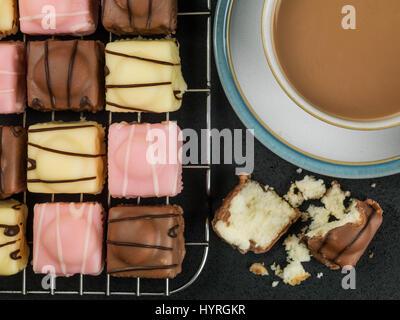 Iced Fondant Fancy Sponge Cakes Against a Black Background - Stock Photo