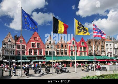 Medieval style shops and restaurants around the market place (Grote Markt) in Bruges Belgium. - Stock Photo
