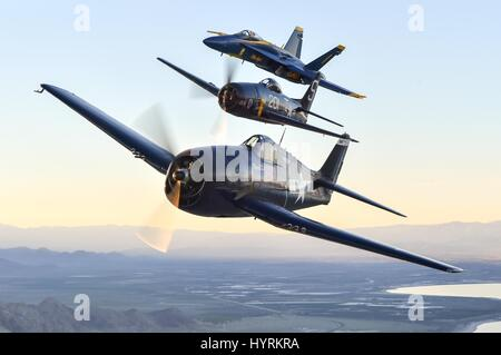A U.S. Navy Blue Angels F/A-18 Hornet fighter aircraft (middle) flies alongside a USN F6F Hellcat World War II-era - Stock Photo