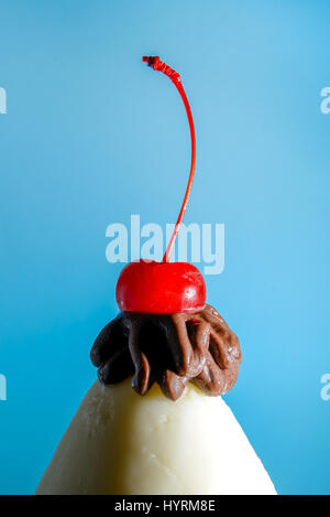 Ice cream cone with chocolate and a cherry on top in front of a blue background. - Stock Photo