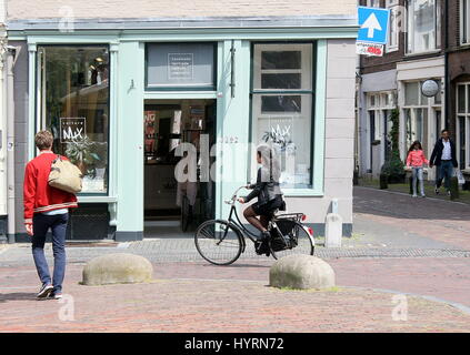Young student girl cycling at Oudegracht Canal, inner city of Utrecht, Netherlands - Stock Photo