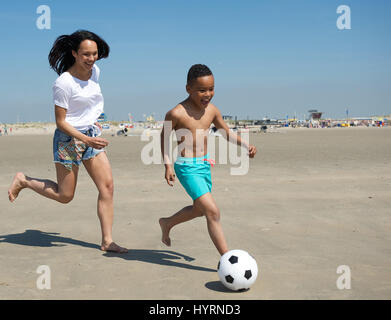 Happy mother and son running on beach with ball in summer - Stock Photo