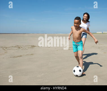 Smiling little boy playing with ball on beach together with mother - Stock Photo