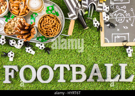salty snacks and drinks on the metal tray for soccer party. - Stock Photo