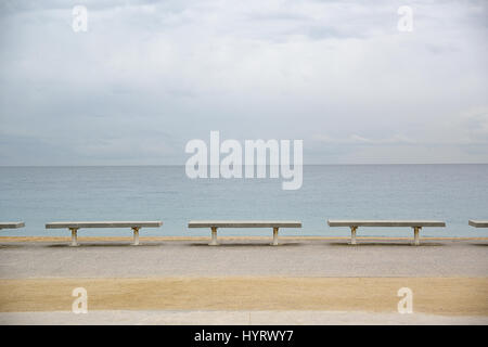 Row of benches next to the sea. Cloudy blue sky. Empty copy space for Editor's text. - Stock Photo