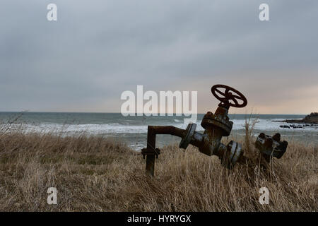 Shabla coast in a cold winter afternoon. Old rusty pipe with valve. - Stock Photo