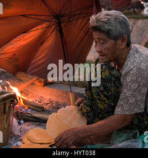 Square portrait of a poor lady making sweet rice pancakes on the street in Cambodia. - Stock Photo