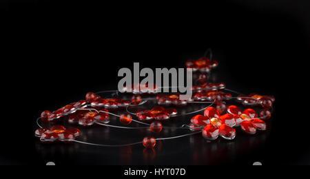 Handmade craft necklace, red flower shape on black background