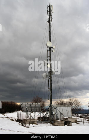 Antenna tower in stormy winter day - Stock Photo