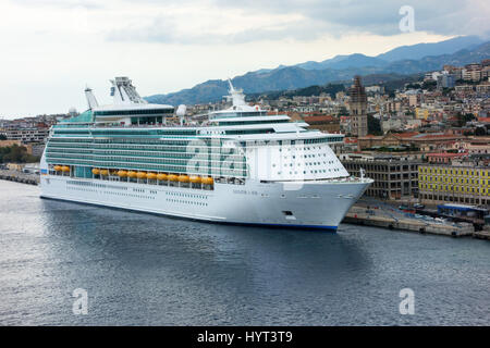 Navigator of the Seas (Royal Caribbean Cruise Lines) cruise ship docked at port and overlooking the town of Messina. - Stock Photo