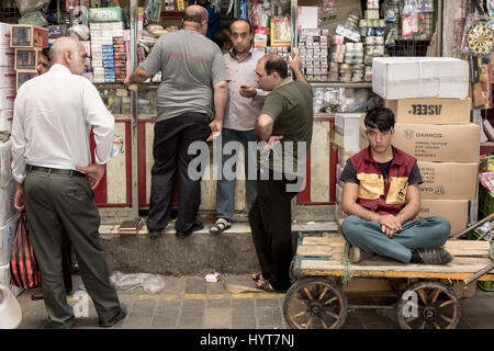 TEHRAN, IRAN - AUGUST 14, 2016: Merchants and delivery boys having a break and discussing in a covered street of - Stock Photo