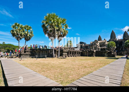Horizontal view of people entering the main entrance of Angkor Wat in Cambodia. - Stock Photo